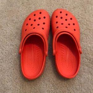 One pair of orange crocs